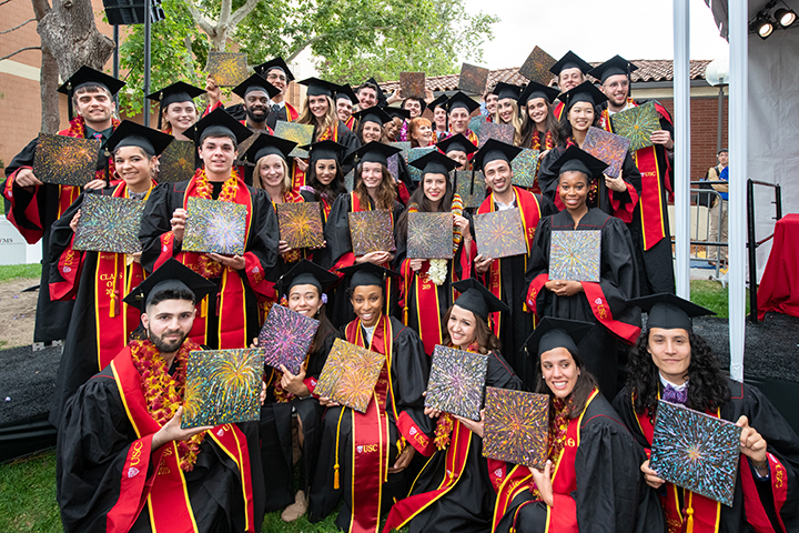 graduates wearing black caps and gowns pose with original paintings