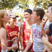 Students laughing and smiling in USC colored clothes