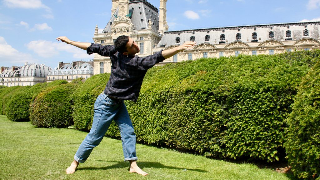 barefoot dancer reaching arms out wearing gray flannel shirt and blue jeans in front of green bushes