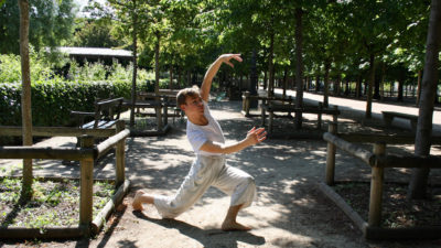 A boy dances in a park lined with trees and brown fences