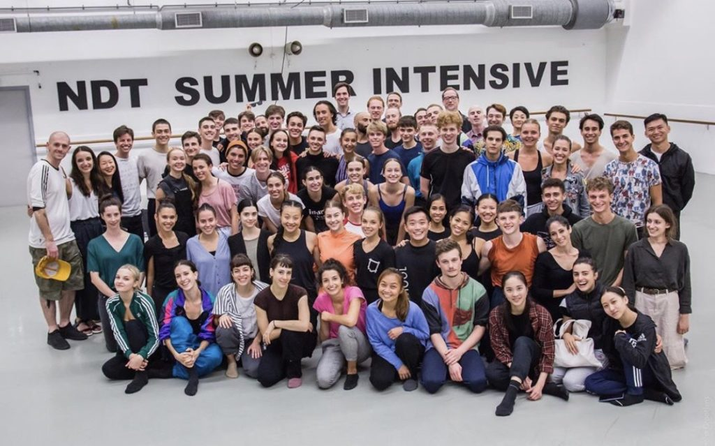 group of people pose in front white wall that says NDT Summer Intensive in black lettering
