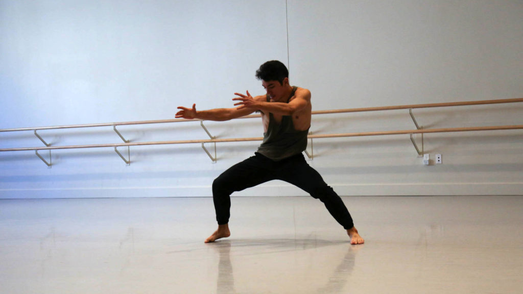 barefoot dancer wearing a green tank top and black pants with arms stretched out