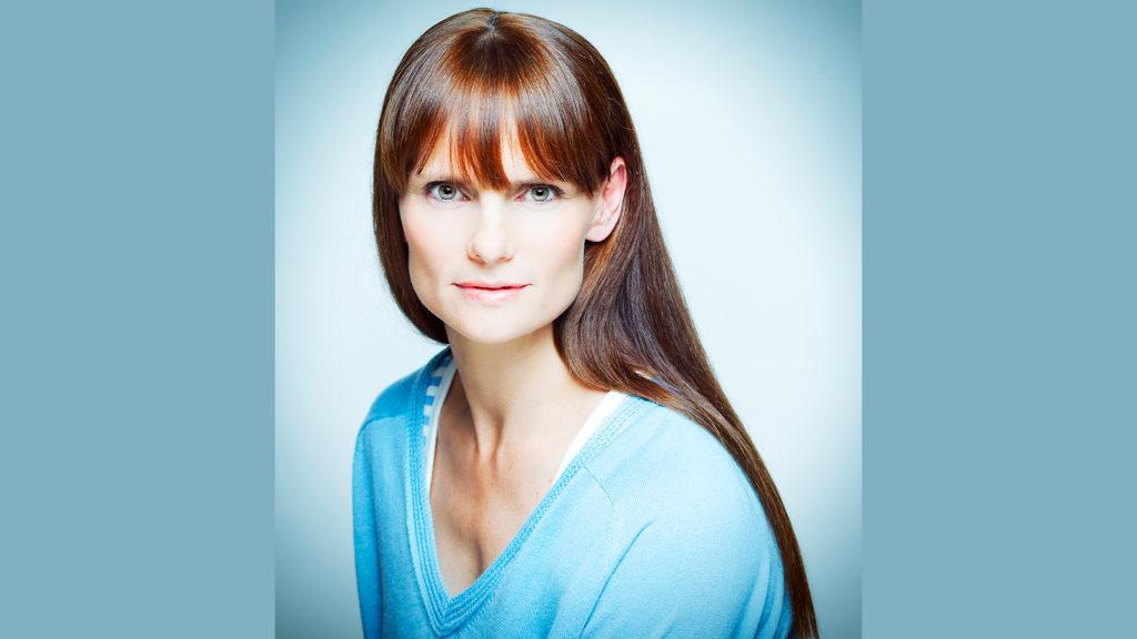 Kate Dunn wearing blue v-neck shirt