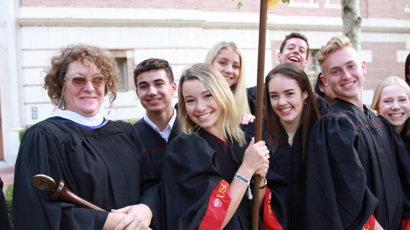 Dawn Stopiello and a group of USC Kaufman students in convocation robes smile for the camera