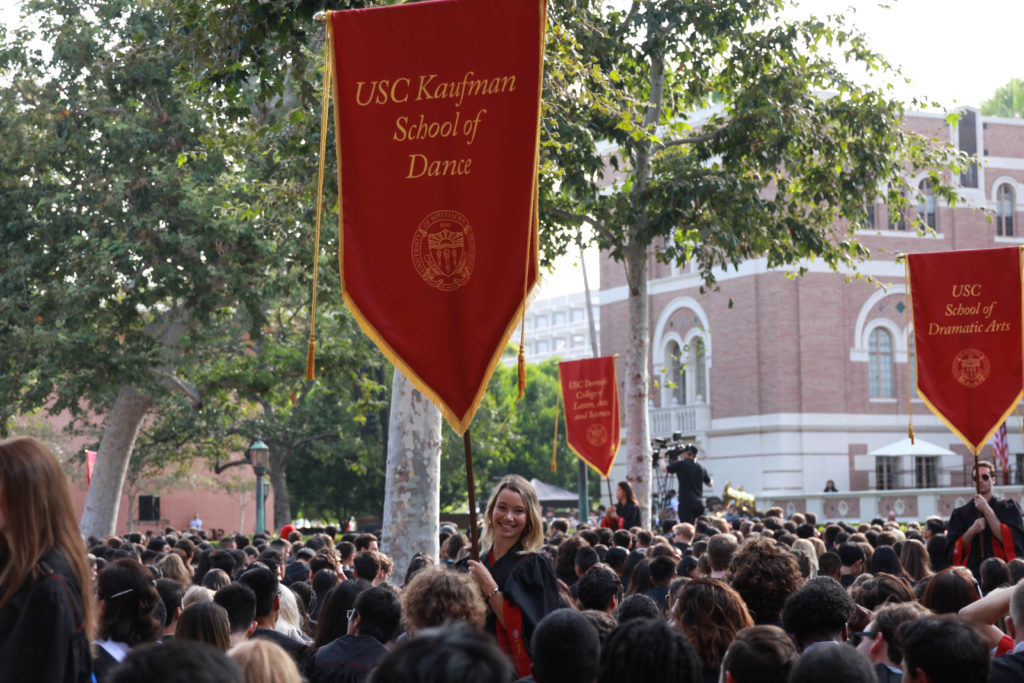 """Above a crowd of students, a girl hold up a red banner with """"USC Kaufman School of Dance"""" embroidered in gold on it"""