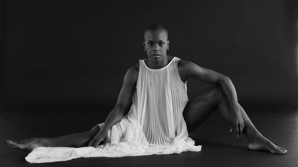 black and white photo of Hope Boykin sitting on the floor wearing a long white dress