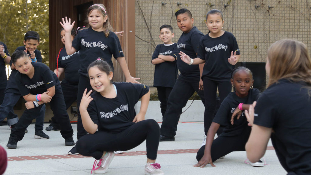 "a group of of kids in black t-shirts that say ""Dance On!"" pose at the end of their performance"