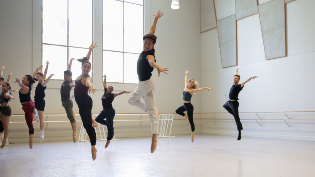 Zackery and a group of dance students jump in passe, with their arms extended to create a 90 degree angle