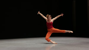 India, in a red tank top and orange capris, dances alone on a dark stage