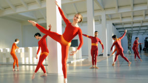 Dancers in red, orange, and yellow unitards strike geometrical poses throughout a white, industrial space