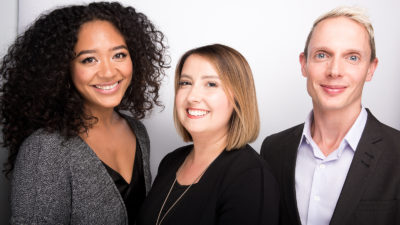 Leanna, Anne and Elliott pose in front of a white background