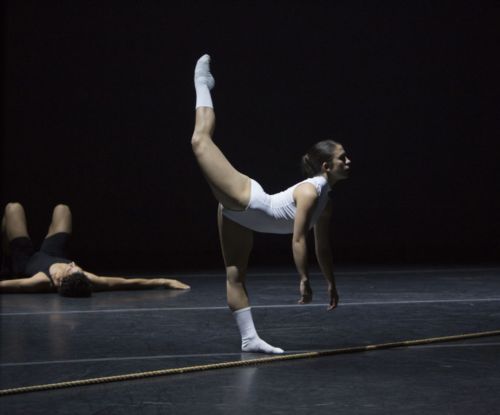 A dancer in white poses with one leg extended up in the air behind them
