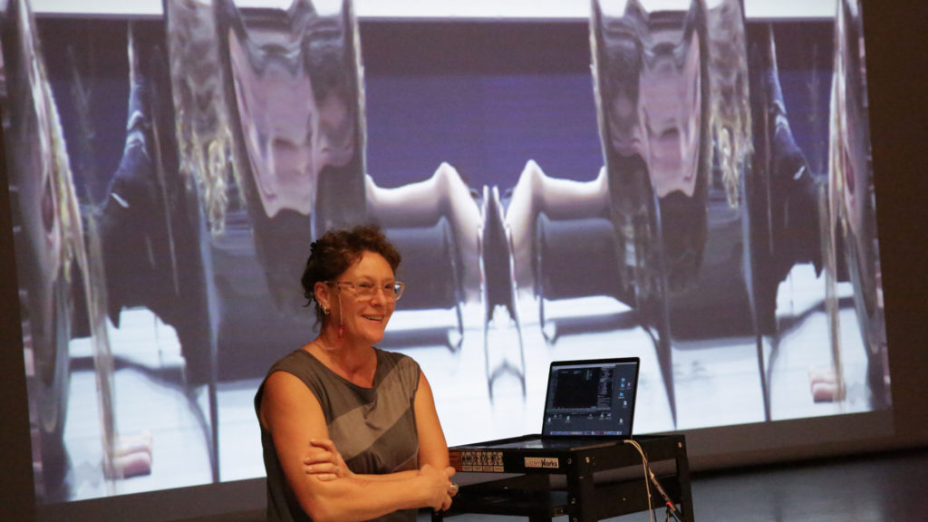 Dawn Stoppiello smiles with arms crossed in front of video projection