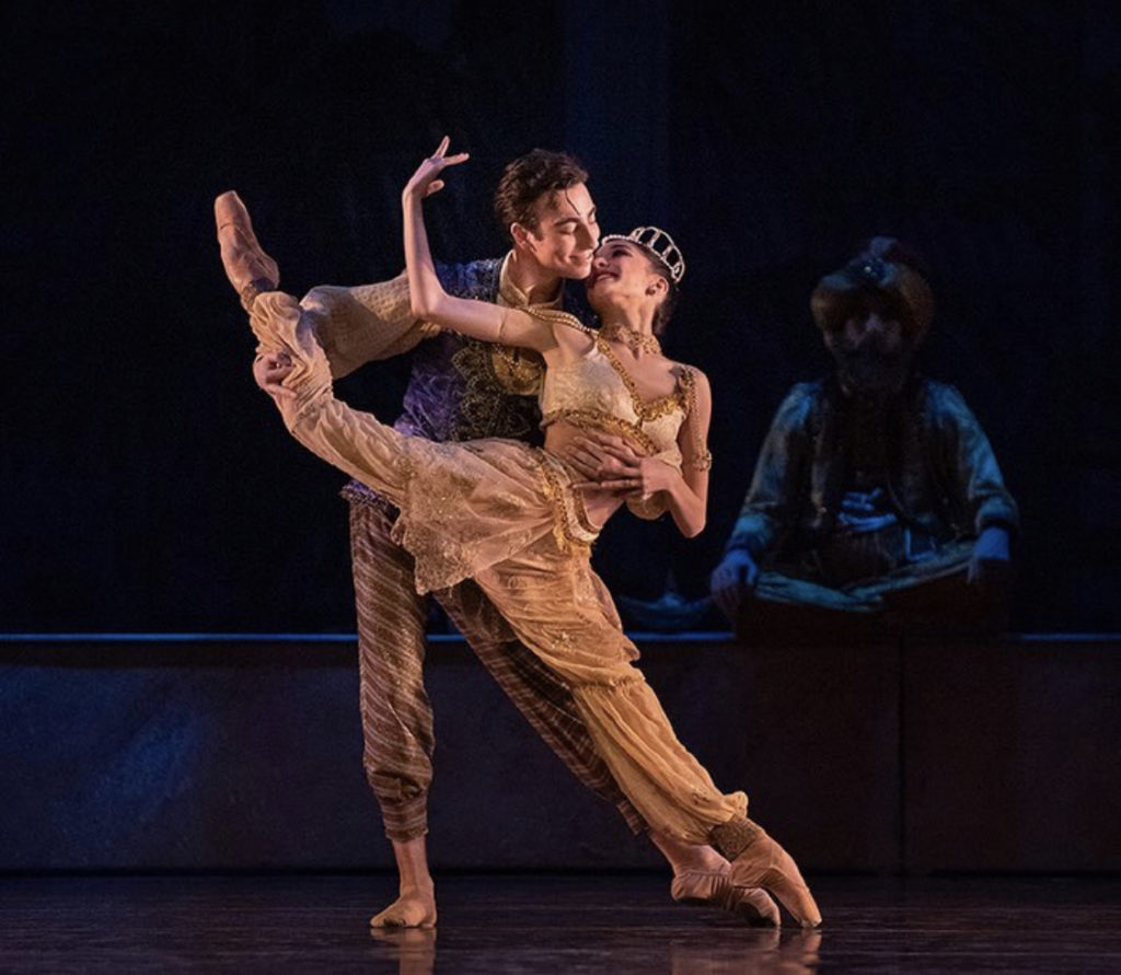 One ballet dancer partners the other in a split
