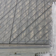 Isabella poses in fourth position en point by a fountain in front of the Louvre