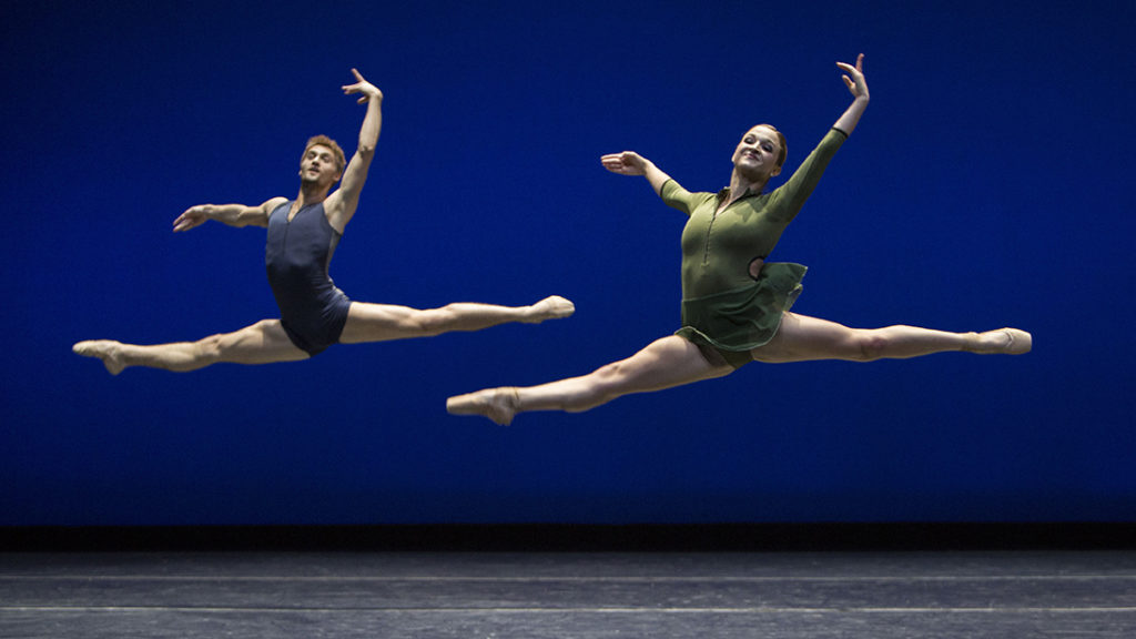 two dancers leaping against a blue backdrop