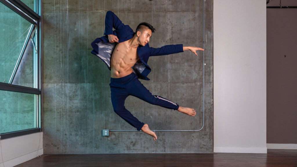 A dancer in blue jumps in front of a grey concrete wall