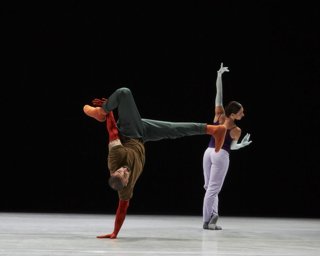 A dancer balances upside down on one hand with one leg bent behind them and one extended forward