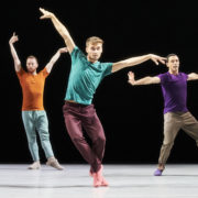 Three dancers in brightly colored t shirts and pants strike angular poses