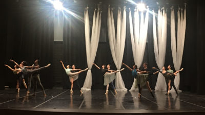 6 dancing couples pose in a partnered arabesque on a rehearsal stage