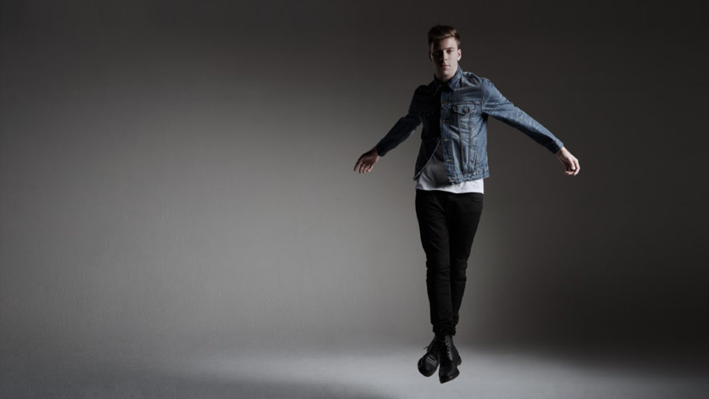 Andrew Winghart jumping in denim jacket and black pants