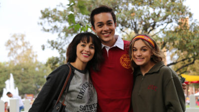 Zack Torres wearing cardinal polo smiling with mother and sister