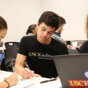 students writing and looking at a computer