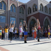 A large group of dancers outside of the Glorya Kaufman International Dance Center balance with their arms extended above their heads