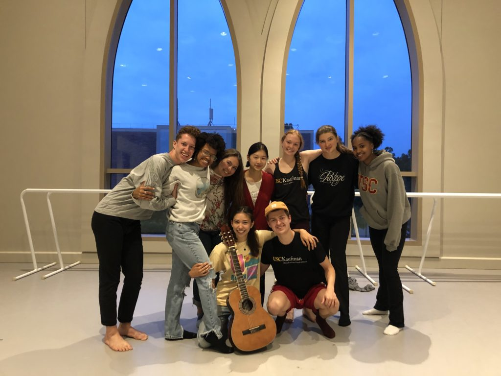 Students pose in a group in a dance studio. One has a guitar