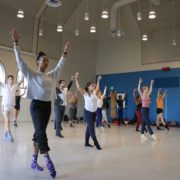 Dance students in their teacher stretch in a circle in a dance studio
