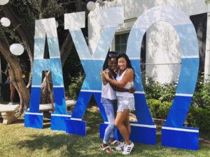 Lenai and Makayla hug in front of AXO sign