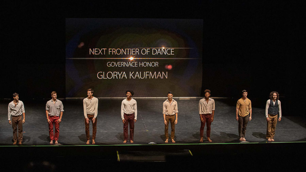 8 dancers stand in a line at the front of the stage