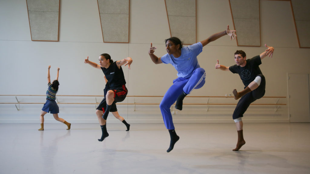 Four dancers rehearse in a studio