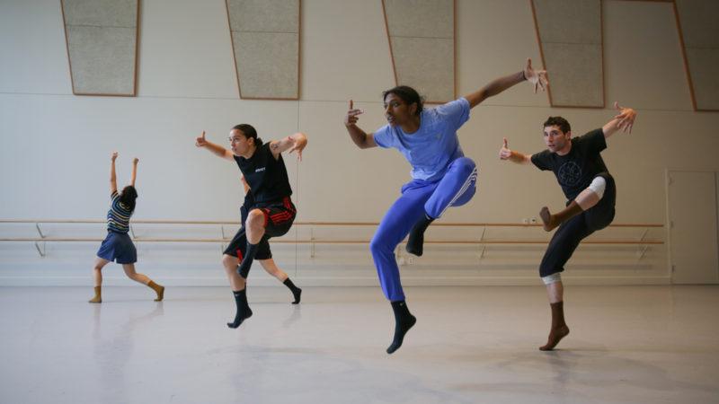 Four dancers rehearse in a studio