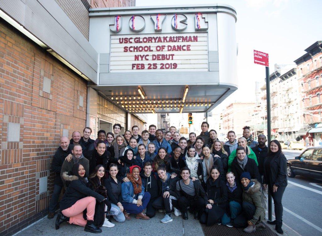 group of people pose under the marquee of The Joyce Theater