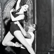 black and white photo of one dancer lifting another wearing pointe shoes