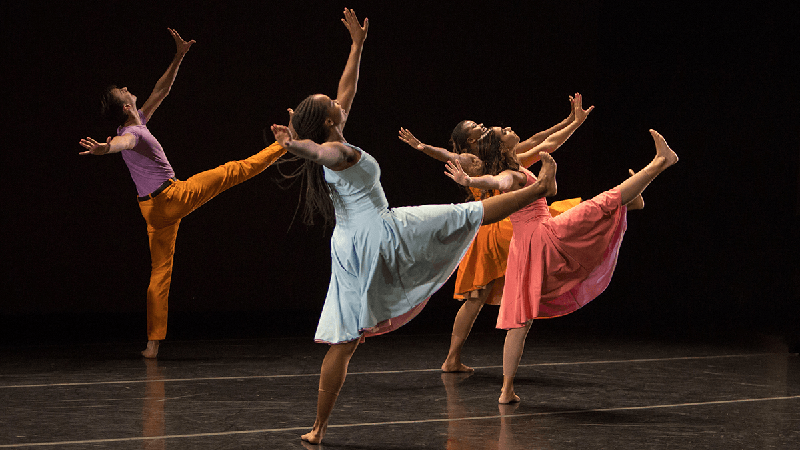 dancers with right legs and both arms in air