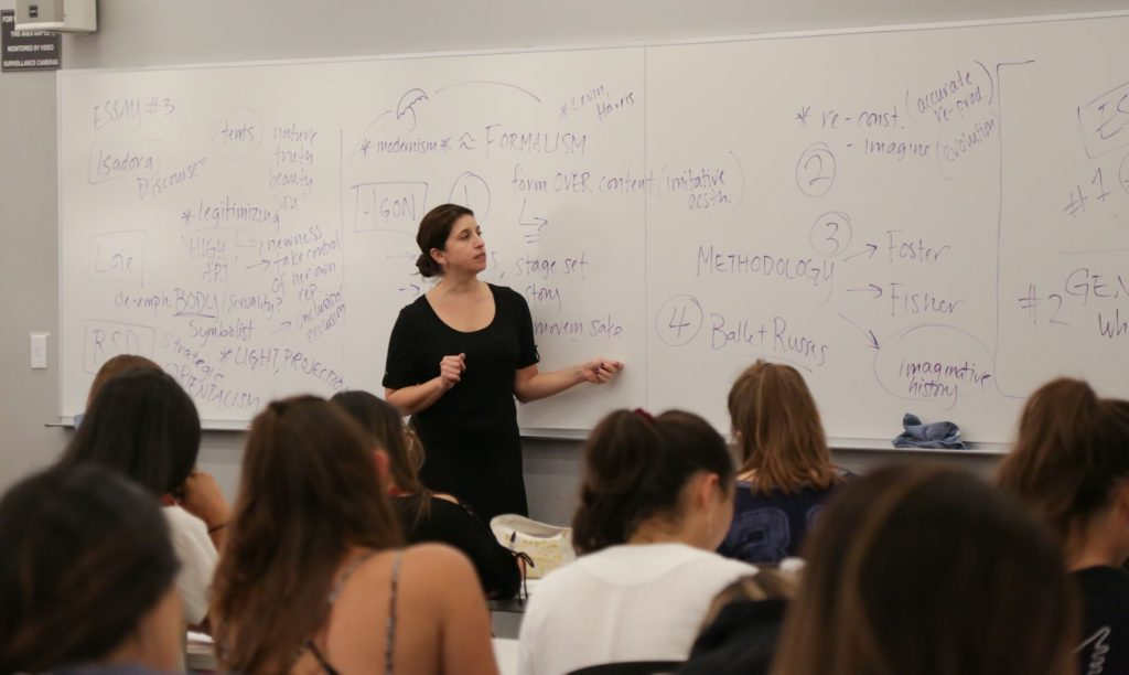 A teacher lectures at the white board
