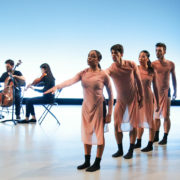 four dancers perform in front of seated musicians