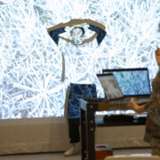 A student stands in front of an artistic projection on the wall