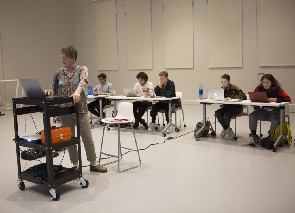 Dawn Stoppiello stands at the projector in front of a row of her students