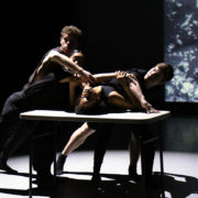 four students dancing in front around a table in front of a projection