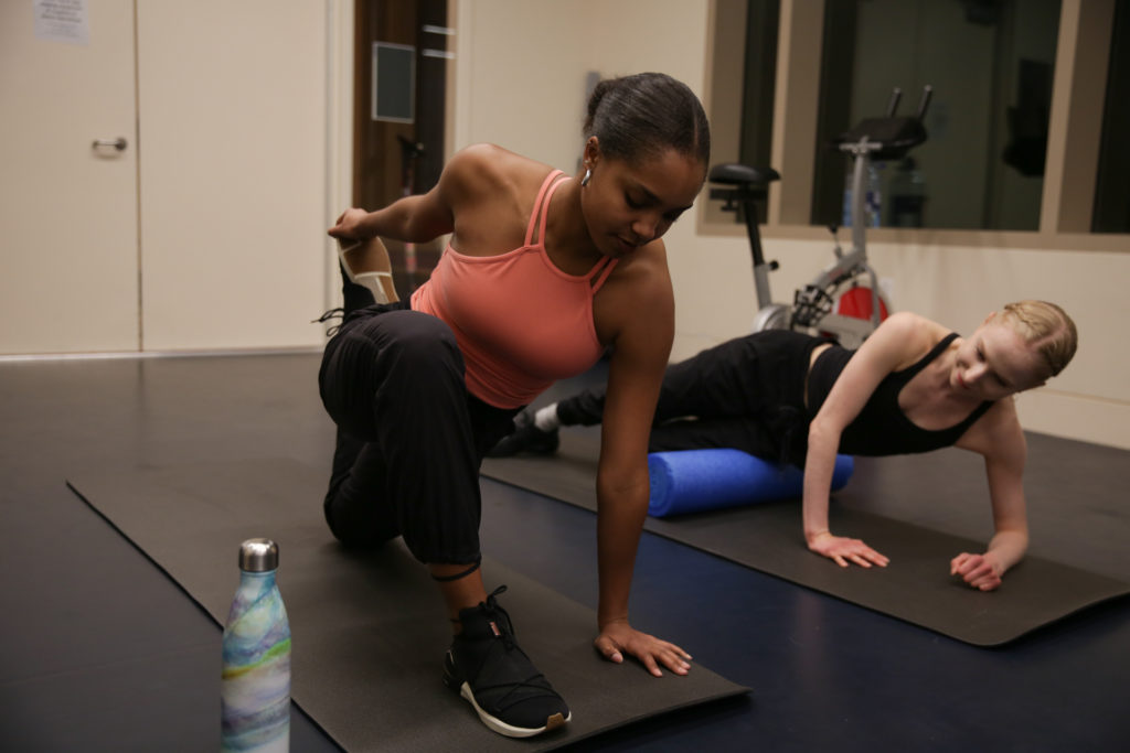 Two dancers stretch and roll out in the Fitness Zone