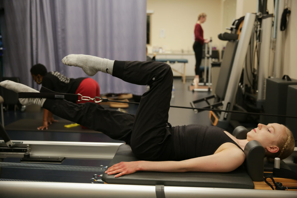 Madison Falconer lies on her back to use the Reformer