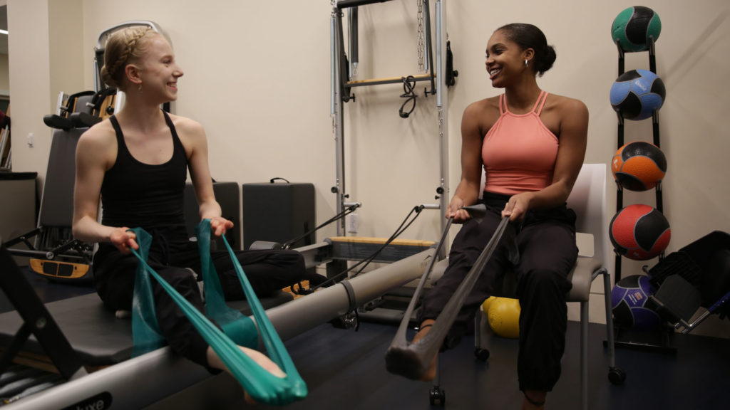 Two dancers use TheraBands in a fitness room