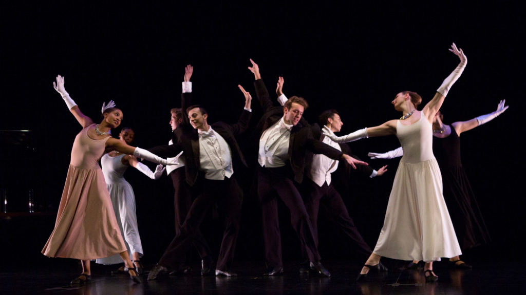 Dancers in formal attire perform in a group on stage