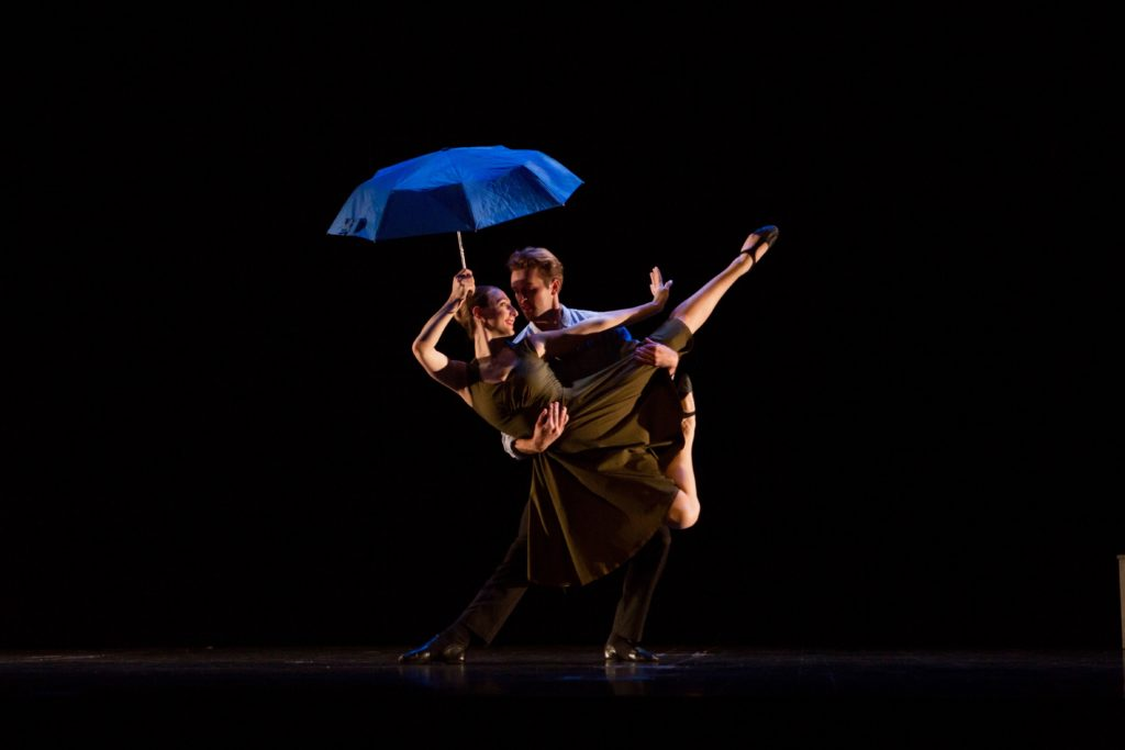 Two dancers partner on stage, one holding an umbrella