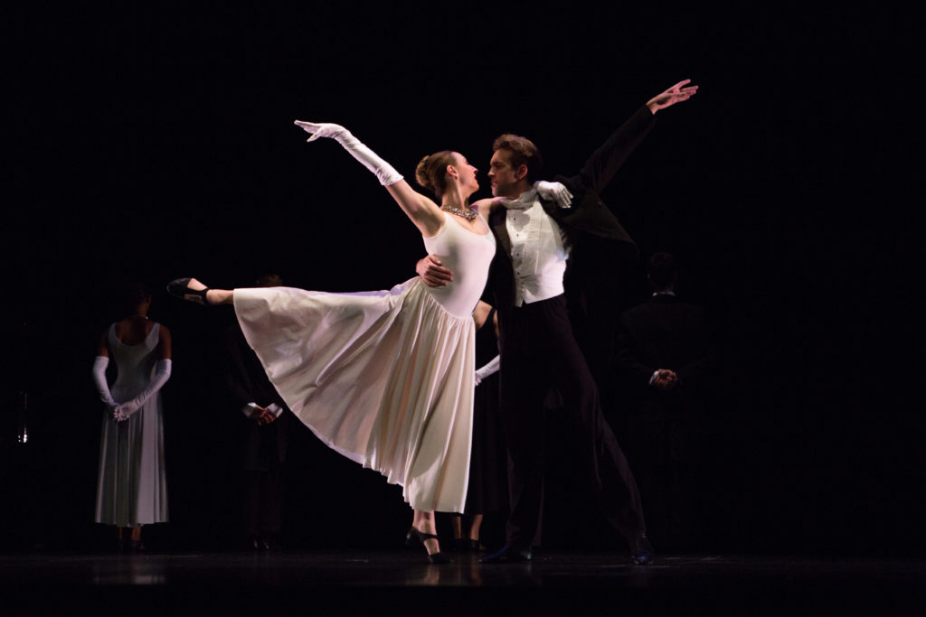 Two dancers in formal attire partner onstage