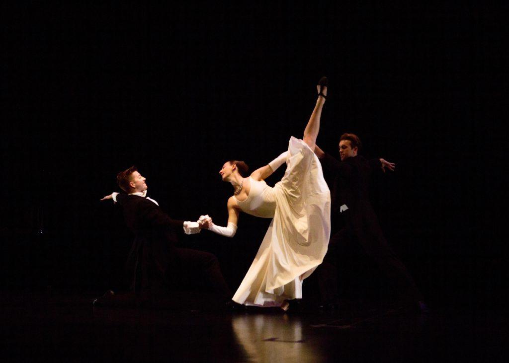 Three dancers in formal attire partner onstage