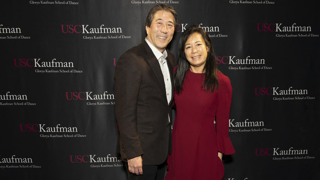 Rod and Elsie Nakamoto smile in front of a USC Kaufman step and repeat